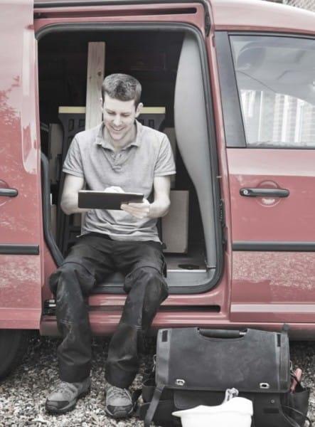 Montør sidder i varevogn med tablet